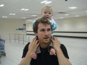 Dad and baby wait in airline waiting area for mum to arrive