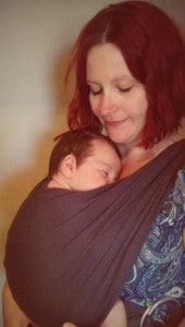 Happy looking mum with sleeping baby in a pouch style baby carrier