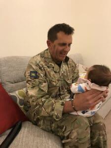 smiling daddy holding newborn