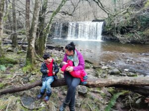 Mum sat and nursing a baby with an older child on a tree branch in the woods, with a waterfall behind