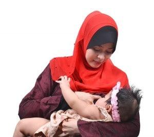 Woman in headscarf breastfeeding baby in pink headband