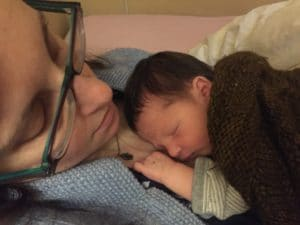 Newborn sleeping on mother's chest, mother looking down.