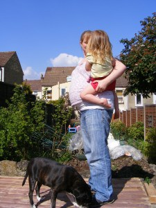 Mother outside holding toddler with dog at her feet