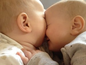 Twin babies with their faces pressed together