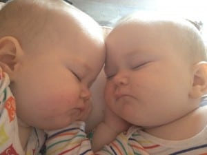 Twins asleep with faces touching