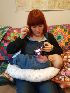 Mother breastfeeding baby while also sewing