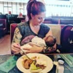 Mother eating in a restaurant while breastfeeding her small baby