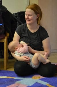 smiling mother kneeling on floor feeding baby
