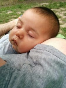 Happy sleeping baby on parent's shoulder
